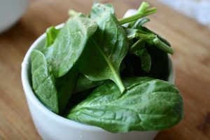 green fresh spinach in a white glass